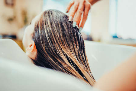 girl in a beauty salon. wash your hair, hair care, health. Toned image. Process of washing your hair in a hairdresser