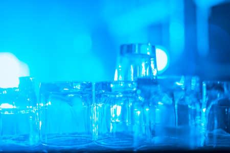 Concetto di partito. Molti bicchieri lavati puliti per bevande forti sul bar alla luce blu. immagine sfocata. Immagine tonica. pronto per una festa Archivio Fotografico