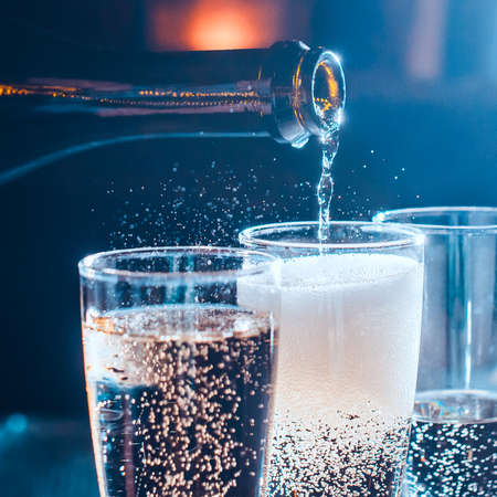 Party and holiday celebration concept. Many glasses of champagne on the table in the restaurant. Toned image. The process of bottling champagne in glasses. close up view