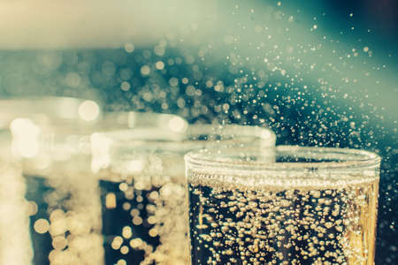 Party and holiday celebration concept. Many glasses of champagne on the table in the restaurant. Toned image. The process of bottling champagne in glasses. bubbles view from the side close up view Stock Photo