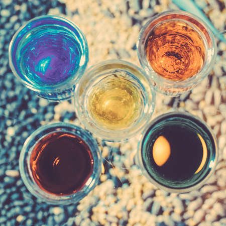 Party and holiday celebration concept. Toned image. Image of multicolored liqueurs in glasses on a wooden stand behind the bar with blurred background. from the top square cropping.