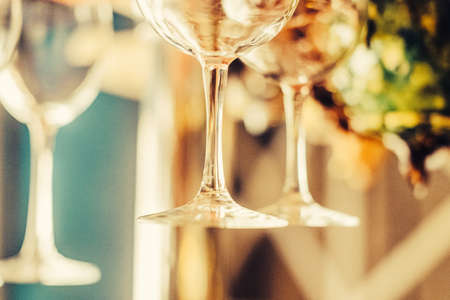 Party concept. Many clean washed glasses for wine on the bar with blurred background. Toned image. close up view with blurred background