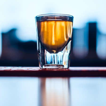 Concetto di drink di benvenuto. Singolo colpo di whisky sulla barra con sfondo sfocato. Immagine tonica.