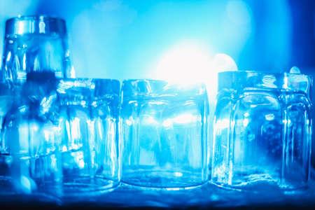Concetto di partito. Molti bicchieri lavati puliti per bevande forti sul bar alla luce blu. immagine sfocata. pronto per una festa