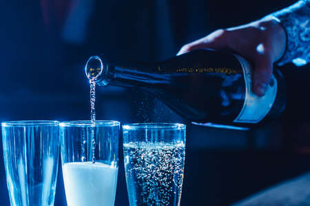 Party and holiday celebration concept. Many glasses of champagne on the table in the restaurant. The process of bottling champagne in glasses. with the hand of the waiter Stock Photo