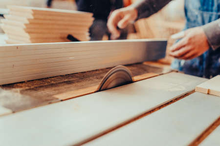 A carpenter works on woodworking the machine tool. Toned image. Man collects furniture boxes. Saws furniture details with bare saw blade view