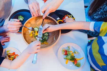 healthy food, family, children, hapiness and people concept - happy family with two kids making and eating fresh salad at home. bowl with salad and many hands from the top close view
