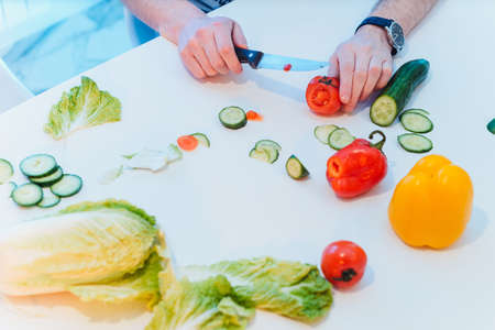 healthy food, family, children, hapiness and people concept - happy family with two kids making dinner at home. Daddy at table cuts vegetables close up view Фото со стока