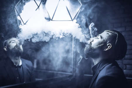 Blond man with a beard in a blue suit strolling on the streets of the city with vaping device. Toned image. success confidence lifestyle concept. portrait of a man vaper with cloud of smoke close up