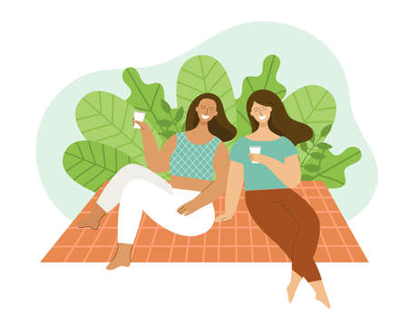 Two young women are sitting on a plaid in a park. Friends are laughing and talking. Concept of a picnic, relaxing at the weekend. Basket with food, hat and ball.