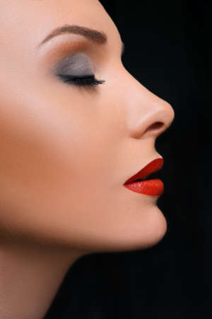 Beauty Close-up Portrait of a Beautiful Fashion Woman Make-up and Red Lips on a Black Background. Bright Color