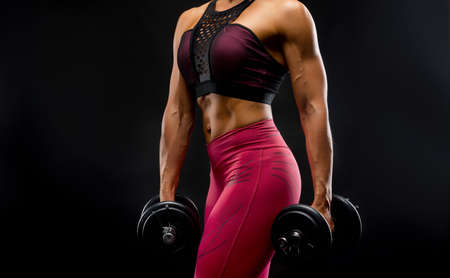 Perfect Fitness Body of Beautiful Woman in Drops. Fitness-instructor in Sports Clothing. Female Model with Fit Muscular and Slim Body in Sportswear. Young Fit Girl Lifting