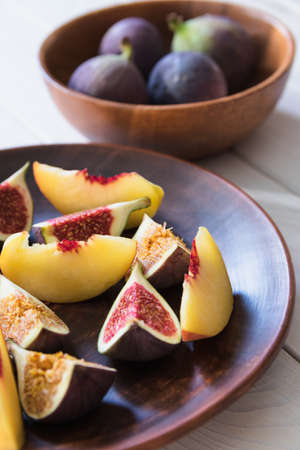 Slices of figs and peaches are in a clay plate on a light wooden table . Autumn fruits. Vegetarianism