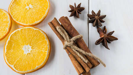 Dried lemon slices, anise starlets and cinnamon on a light wooden table