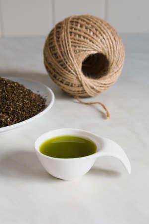Natural hemp oil in a white ceramic spoon, hemp fiber and natural hemp thread.