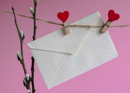 An empty cardboard envelope is hung with wooden clothespins with a red heart and a willow branch on a pink background. Easter holiday concept Stock fotó