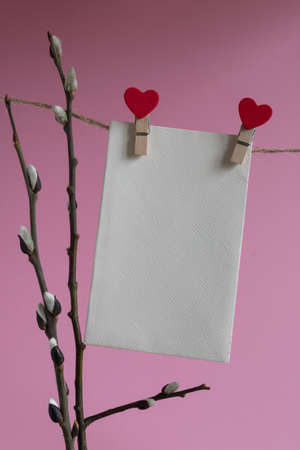 An empty cardboard envelope is hung with wooden clothespins with a red heart and a willow branch on a pink background. Easter holiday concept