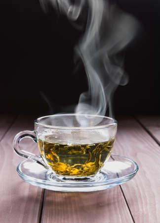 Una tazza trasparente di tè verde caldo con foglie grandi e vapore su sfondo scuro. Minimalismo. Orientamento verticale