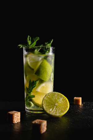 A glass of cold mojito cocktail with mint leaves and cubes of cane sugar on a black background.