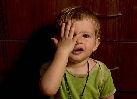niños rubios: Niño pequeño juguetón cierra los ojos una mano en broma Foto de archivo