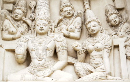 Sculptural images of Shiva and Parvati in accompaniment of the retinue on the wall of an ancient Indian temple