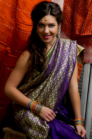 The young dark-haired woman in the rich Indian saris and colorful bracelets smiling sitting on a background of silk screen. Indian style. Stock Photo
