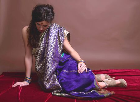 The young dark-haired woman in a bright Indian sari sitting musingly bowed her head. Indian style.