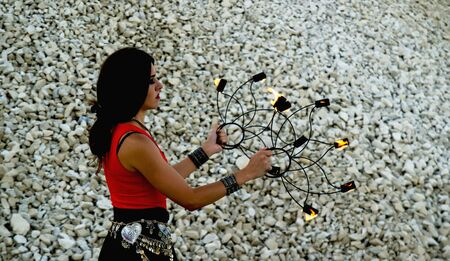 The young dark-haired woman in a bright red top and ethnic jewelery holding fans of the torches on the background wall of small stones.