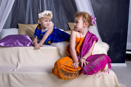 Two little sister girls in ethnic clothes look at each other sitting among pillows on a stepped dais