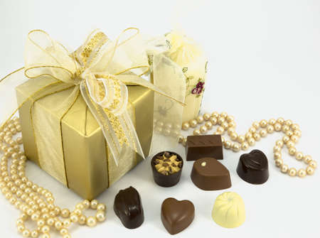 Gold gift with pearls and assorted chocolates. photo