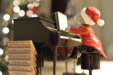 Een muis draagt ??een kerstman-pak en speelt kerstliederen op een piano. Stockfoto