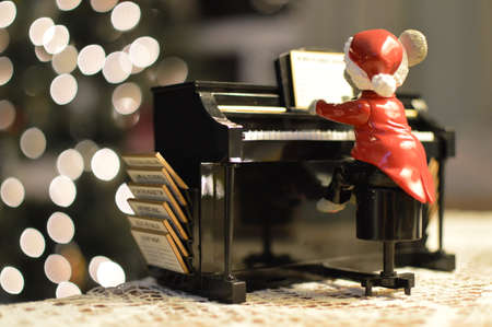 A mouse wearing a Santa suit playing Christmas Carols on a piano.