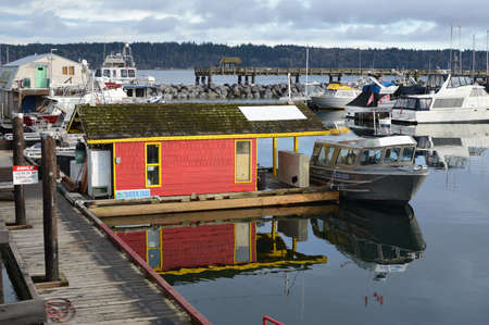 reflective: Marina with reflective calm waters on the east coast of Vancouver Island . Editorial