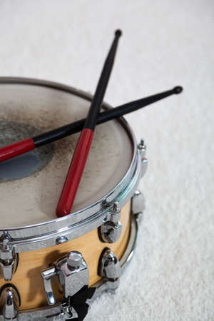 Snare drum with drum sticks on a white background