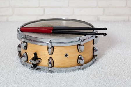 Snare drum with drum sticks on brick wall background Stock Photo