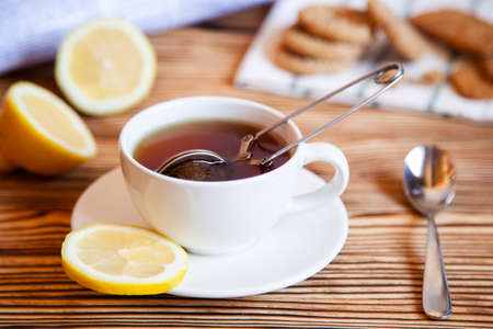 Cap of tea with lemon and cookies on the wooden table. Teatime.