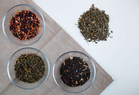 Assortment of dry tea in round bowls on a white background. Top view.