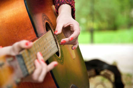 girl playing guitar: girl playing guitar in the park