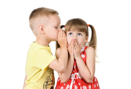 secret: Boy whispers a secret in the ear of the girl