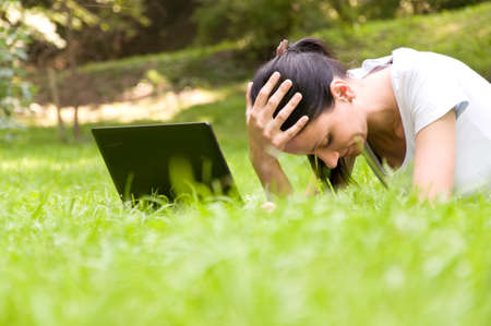 difficult decision: Girl freelancer doing her job in the park. a difficult decision Stock Photo