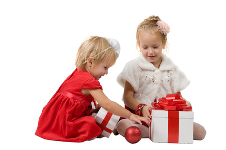 caja blanca: Christmas. Two little girls open white box with a gift Foto de archivo