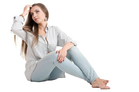 ragazze a piedi nudi: bella ragazza seducente con lunghi capelli castani, seduta sul pavimento in blue jeans. isolato