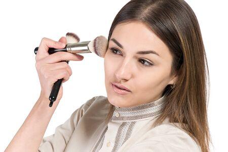 visagiste: visagiste. young girl paints her eyes. Girl doing makeup. isolate