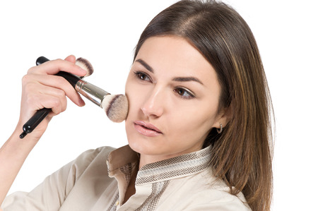 luxuriant: visagiste. young girl paints her eyes. Girl doing makeup. isolate