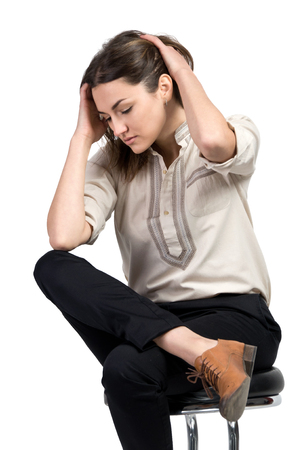confident business woman: Business woman dressed in black trousers and brown shoes sits in a chair Stock Photo