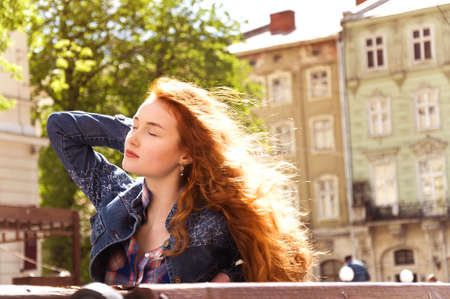 hair wind: girl with red curly hair. wind blew away hair
