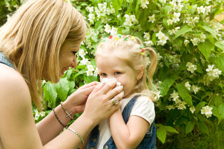 serviette: The girl is allergic to pollen. Mom wiped her nose with a serviette Stock Photo