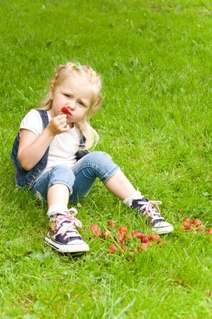 little girl eating a strawberry in nature. in the park Stock Photo