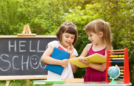 Two little girls reading a book on the nature and talking Stock Photo