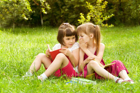 Holčičky čtení knih na trávníku a říct si navzájem něco zajímavého Reklamní fotografie